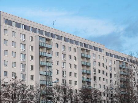 Los árboles desnudos en frente de moderno de poca altura, la construcción de viviendas residenciales con pequeños balcones de la última del día del otoño con el cielo azul