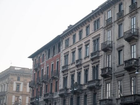 upper floor: Angled Architectural Exterior View of Old Fashioned Low Rise Residential Upper Floor Apartments with Small Balconies in Urban Environment on Overcast Day