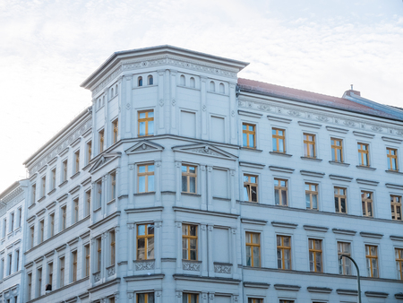 exterior architectural details: Architectural Exterior of Corner of Low Rise White Building with Classical Architecture Details on Facade in Urban Area and Illuminated by Late Day Sun from Behind