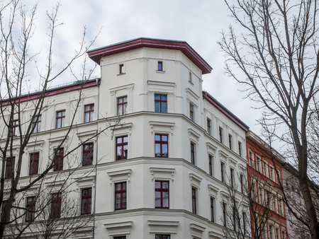 architectural exterior: Architectural Exterior View of Corner of Renovated White Building with Red Trim in Row of Low Rise Buildings in Urban Setting on Overcast Day