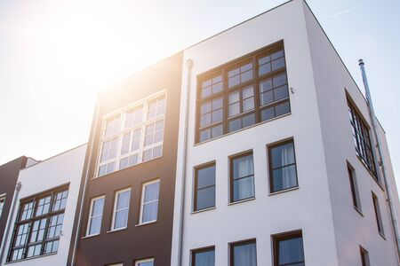 Cute block shaped white and brown apartment buildings from low angle view with bright sunlight over the roof