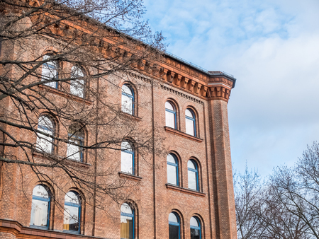cornice: Architectural Exterior View of Old Historical Red Brick Building with Decorative Rooftop Cornice Surrounded by Bare Trees and Framed by Cloudy Blue Sky Stock Photo