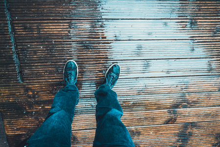 Man standing on a wet wooden deck with a first person perspective looking down at his legs and shoes
