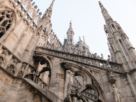buttresses: Low Angle Architectural Detail of Italian Gothic Flying Buttresses and Spires of Historic Milan Cathedral Church, Dedicated to St Mary of the Nativity, Milan, Italy