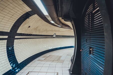 after hours: Architectural background of an empty enclosed tunnel or walkway with curved tiled walls and floor curving away to the right in a receding perspective