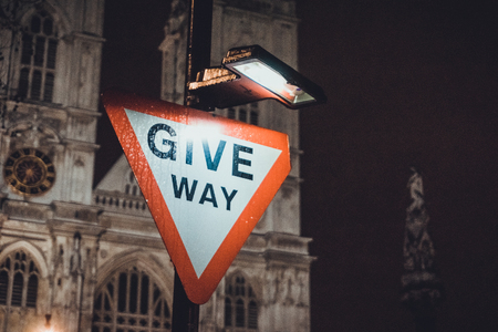 give the way: Give Way traffic warning sign illuminated at night in front of Westminster Cathedral, London Stock Photo