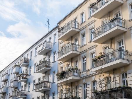 Reihen der angeschlossenen blauen und gelben Wohngebäuden mit hübschen Balkonen und Fenstern an einem sonnigen Tag