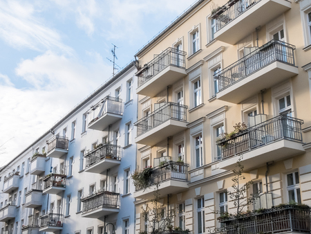 Rows of connected blue and yellow residential buildings with pretty balconies and windows on sunny day