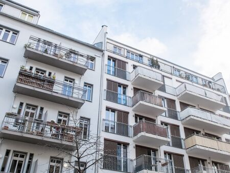 exterior architectural details: Low angle view of modern white apartment complex with balconies and ribbed facades during day Stock Photo