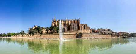 panoramic sky: Panoramic View of Historic Santa Maria of Palma Cathedral, or La Seu, Reflected in Green Fountain Water on Sunny Day with Clear Blue Sky in Mallorca, Spain Stock Photo