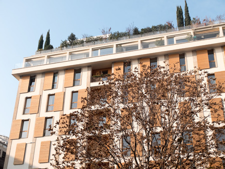 architectural exterior: Low Angle Architectural Exterior View of Generic Modern Apartment Building with Rooftop Garden and Obscured by Bare Tree on Sunny Autumn Day with Blue Sky