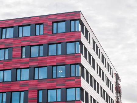 architectural exterior: Low Angle Architectural Exterior View of Modern Low Rise Office Building with Red Patterned Facade and Reflection of Sun on Cloudy Overcast Day
