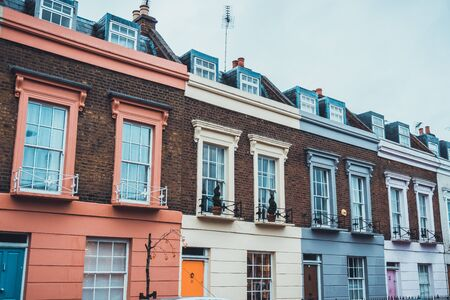 row of houses: Architectural Exterior View of Stylish Luxury Apartments on Upper Floors of Quaint Row Houses Painted in Various Pastel Colors on Gloomy Gray Overcast Day