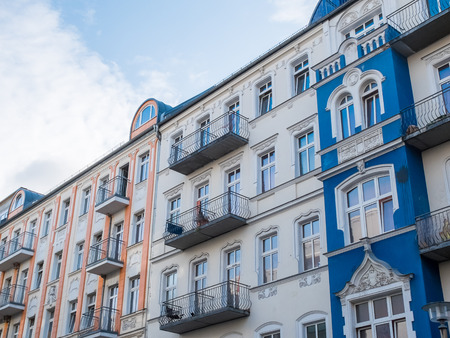 decorative balconies: Long row of blue and pink apartment buildings