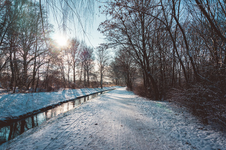 wooded path: Well Traveled Walking or Bike Path Along Side Small Canal River Through Wooded Area on Sunny Winter Day with Clear Blue Sky at Sunrise or Sunset Stock Photo