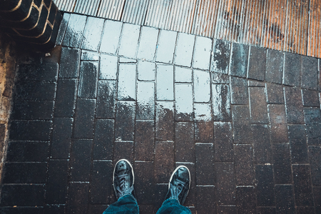 personal perspective: High Angle View and Personal Perspective of Man Looking Down at Feet in Sneakers Standing on Wet Rainy Brick Patio or Sidewalk Surface, with Copy Space Stock Photo