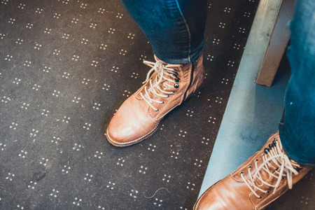carpeting: High angle first person perspective detail view of brown leather boots and jeans of person standing on dirty mat on metal floor