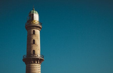 tranquil atmosphere: Exterior view of old tall lighthouse beacon with copy space in clear blue sky Stock Photo