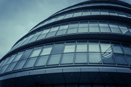 extreme angle: Extreme Close Up and Low Angle Architectural Exterior View of Modern City Hall with Rounded Facade in London, England with Gloomy Gray Overcast Sky in Background