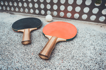 Two wooden ping pong bats and ball on an outdoor table with a perforated metal net conceptual of sport and an active lifestyle Imagens
