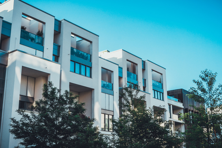 Row of luxury modern white townhouses with large windows and recessed balconies in a leafy green suburb under a clear sunny blue sky