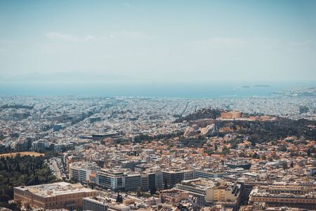 Birds eye view of sprawling residential, commercial and historical buildings and streets in Athens Greece with ocean in the distant background
