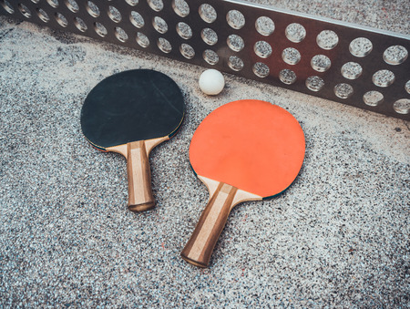 Table tennis  ball with red and black bats on an outdoor table with a metal net in a close up view