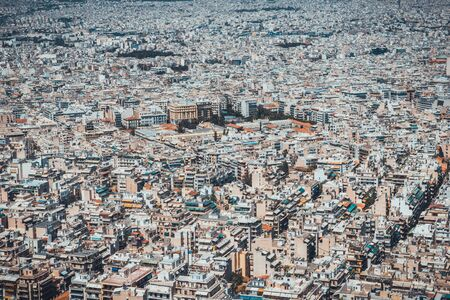 Birds eye view of sprawling residential, commercial and historical buildings and streets in Athens Greece