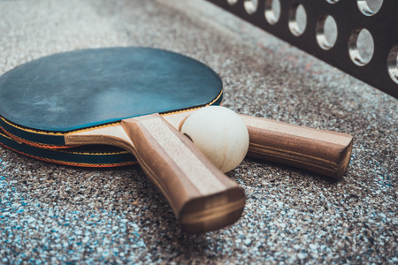 Two wooden table tennis bats with a ball lying together on an outdoor table tennis table with the handles facing the camera
