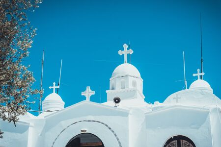 White greek orthodox church with crosses on domed cupolas against a clear sunny blue sky, low angle view of the rooftop Imagens