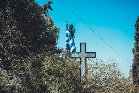 Close Up of Religious Cross and Blue and White Striped Flag of Greece Surrounded by Lush Green Tree Branches on Sunny Day with Clear Blue Sky in Greece