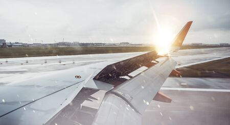Sun rising over the wing tip of an aircraft on the runway of an airport in a concept of travel