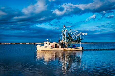 shrimpboat leaving port for a days work in the gulf of mexico
