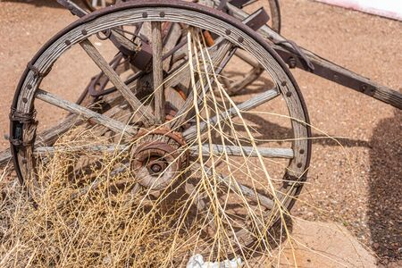 old broke down wagon wheel with tumble weed in spokes