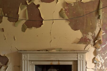 Peeling paint on the walls above a fireplace in a decaying old mansion house. Dumfries, Scotland.