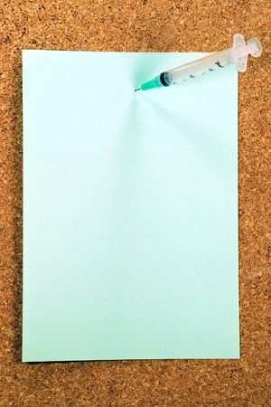 A green paper note held by a syringe on a cork medical bulletin board Stock Photo - 6873833