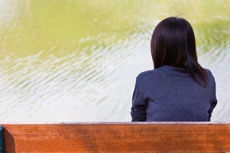 mirada triste: chica sola cerca del río Foto de archivo