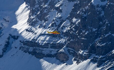 A yellow rescue helicopter is flying over the Alps in winter season