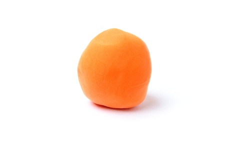 An image of a piece of orange plasticine on white background Stock Photo