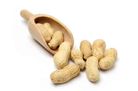 An image of peanuts in a wooden scoop
