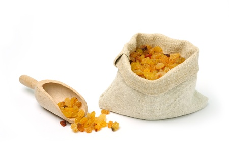 An image of raw yellow raisins in a bag with scoop