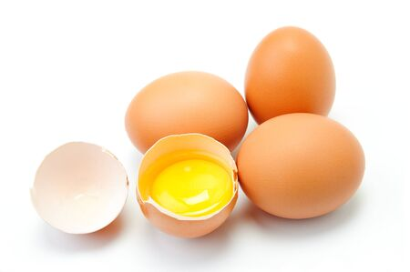 Four eggs on white background. One egg is broken photo
