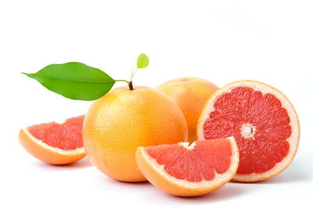 Ripe grapefruit with leaves and slices on white background
