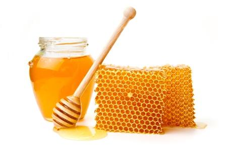 peine: Olla de miel y palo de madera se encuentran en una tabla