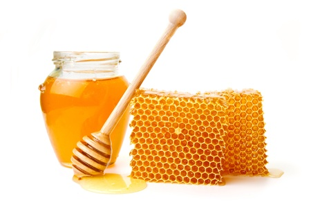 Pot of honey and wooden stick are on a table photo
