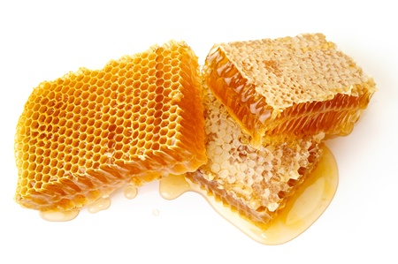 Yellow honeycomb wax cell detail slice on white background