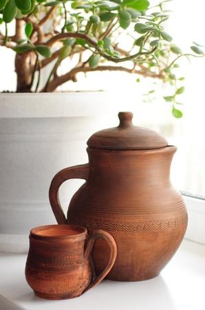 Ñlay jug and mug on the white ûøää Stock Photo