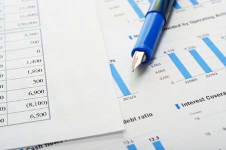 A business financial chart with a pen pointing at a bar graph.  Stock Photo