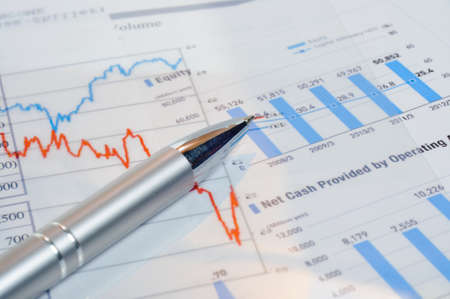 An image of pen on financial newspaper with stock market graphics photo