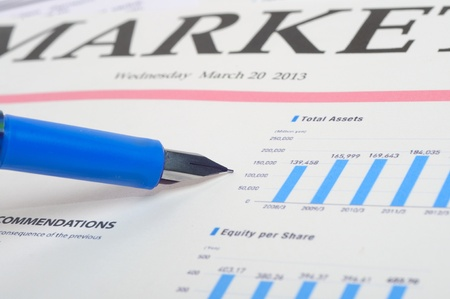An image of pen on financial newspaper with stock market graphics